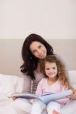 Mère et descendant affichant un livre sur le bâti Images stock