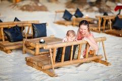 Mère et descendant au café de plage Photographie stock libre de droits