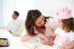 Mère et descendant ayant l'amusement dans la cuisine Images stock