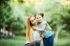 Mère et descendant ayant l'amusement dans le stationnement Concept de la famille heureux Scène de nature de beauté avec le mode d Photographie stock libre de droits