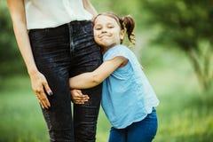 Mère et descendant ayant l'amusement dans le stationnement Fond d'été d'aginst de jambe de mère d'étreinte de fille Images stock