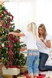 Mère et descendant décorant l'arbre de Noël Photos libres de droits