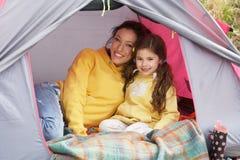 Mère et descendant détendant dans la tente en vacances image libre de droits