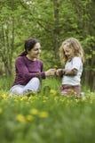 Mère et descendant dans l'herbe avec des fleurs Photos stock