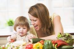 Mère et descendant dans la cuisine effectuant une salade Image libre de droits