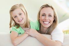Mère et descendant de sourire sur le sofa Photo stock