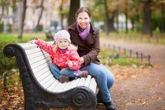 Mère et descendant de sourire sur un banc photographie stock