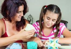 Mère et descendant effectuant l'origami Images stock