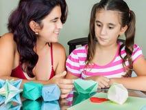Mère et descendant effectuant l'origami Photos stock