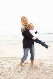 Mère et descendant en vacances ayant l'amusement sur la plage Photographie stock libre de droits