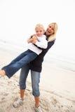 Mère et descendant en vacances ayant l'amusement sur la plage Image libre de droits