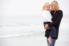 Mère et descendant en vacances restant sur la plage Image stock
