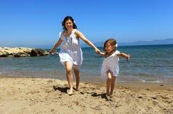 Mère et descendant exécutant sur la plage Images stock