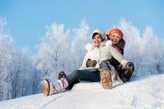 Mère et descendant glissant dans la neige photo stock