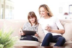 Mère et descendant heureux avec la tablette de Digitals Photographie stock