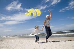 Mère et descendant jouant avec des ballons sur le b Images stock