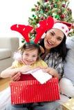 Mère et descendant jouant avec des cadeaux de Noël Images stock