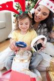 Mère et descendant jouant avec des présents Photos stock