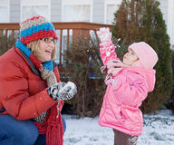 Mère et descendant jouant dans la neige Photos stock