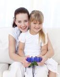 Mère et descendant jouant des jeux vidéo à la maison Photographie stock libre de droits