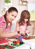 Mère et descendant jouant la pâte à modeler. Photographie stock libre de droits