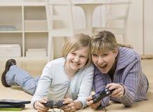 Mère et descendant jouant le jeu vidéo photo stock