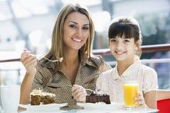 Mère et descendant mangeant le gâteau en café images stock