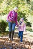 Mère et descendant marchant le long du chemin d'automne Image stock