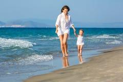 Mère et descendant marchant sur la plage Photographie stock