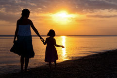 Mère et descendant marchant sur la plage de coucher du soleil Image stock
