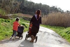 Mère et descendant poussant des landaus Image libre de droits