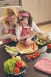 Mère et descendant préparant la salade Photos stock