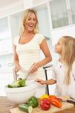 Mère et descendant préparant la salade Photos libres de droits