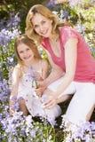 Mère et descendant retenant à l'extérieur des fleurs photographie stock