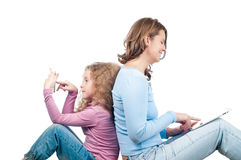 Mère et descendant s'asseyant avec le téléphone et la tablette. Photographie stock libre de droits