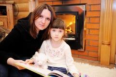 Mère et descendant s'asseyant devant la cheminée Image libre de droits