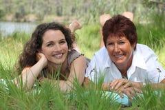 Mère et descendant se situant dans l'herbe images stock