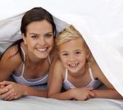 Mère et descendant sous les draps Photographie stock