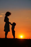 Mère et descendant sur la silhouette de coucher du soleil Image libre de droits