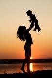 Mère et descendant sur le coucher du soleil Images stock