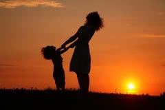 Mère et descendant sur le coucher du soleil observant sur le ciel Image libre de droits