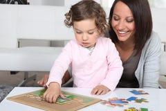 Mère et descendant terminant le puzzle Photographie stock libre de droits