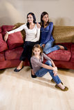Mère et descendants s'asseyant ensemble à la maison en l image stock