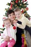 Mère et deux enfants décorant l'arbre de Noël photographie stock