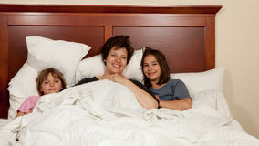 Mère et deux filles dans le lit Photos stock