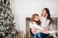 Mère et enfant à l'aide du téléphone intelligent à la communication avec le papa la soirée de Noël photos libres de droits