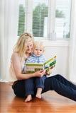 Mère et enfant affichant un livre Photos libres de droits