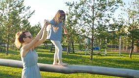 Mère et enfant ayant l'amusement extérieur au coucher du soleil clips vidéos