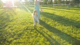 Mère et enfant ayant l'amusement extérieur au coucher du soleil banque de vidéos
