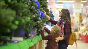 Mère et enfant choisissant l'arbre de Noël dans le supermarché Jeune bel Noël-arbre d'achats de maman et de fille avec clips vidéos